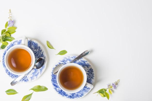 Foglie di tè al limone con tazza e piattino su sfondo bianco