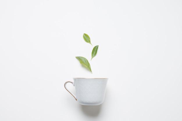 Foglie di tè al limone sopra la tazza di porcellana contro sfondo bianco