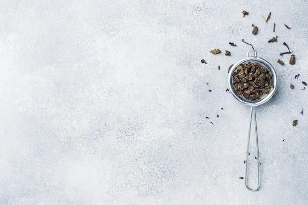 Foglie di tè per la preparazione in un colino su uno sfondo grigio. copia spazio