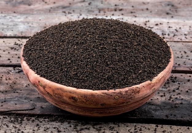 Foglie di tè sciolte o secche del tè nero aromatico sulla tabella di legno