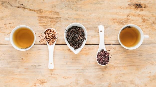 Foglie di tè secche con tè al limone ed erbe disposte in fila sul tavolo