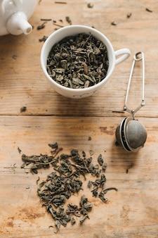 Foglie di tè secche in tazza con colino da tè sul tavolo