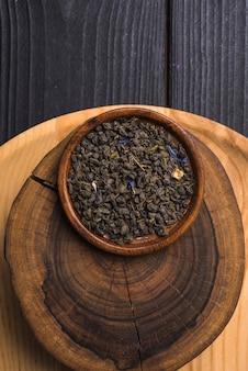Foglie di tè secche sul piatto di legno sopra il ceppo di albero contro la tavola