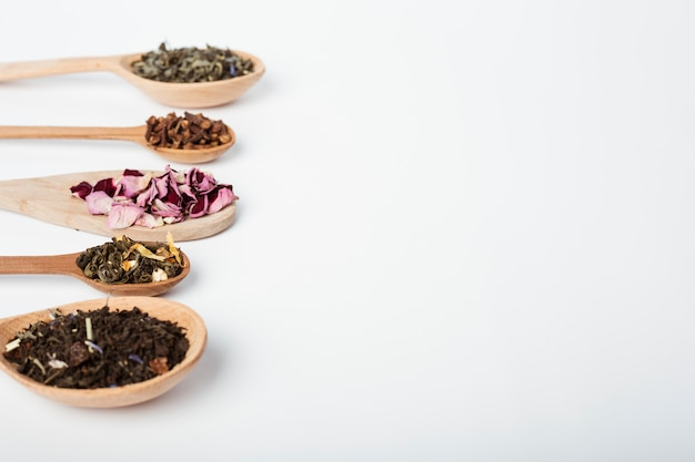 Foglie di tè sul cucchiaio di legno