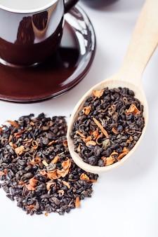 Foglie di tè verdi secche con i petali del fiore in cucchiaio e tazza di legno con il piattino