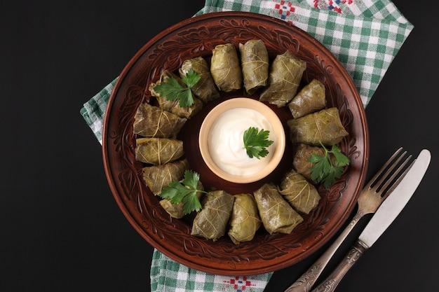Foglie di vite ripiene - cucina tradizionale mediterranea, dolma su un piatto marrone con prezzemolo fresco e salsa all'aglio su sfondo nero, primo piano, vista dall'alto