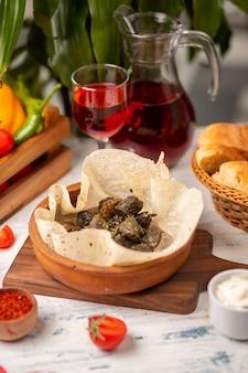 Foglie di vite verdi ripiene di carne, riso, erbe aromatiche, cipolla e olio d'oliva, servite con lavash e pane. yarpag dolmasi, yaprak sarmasi
