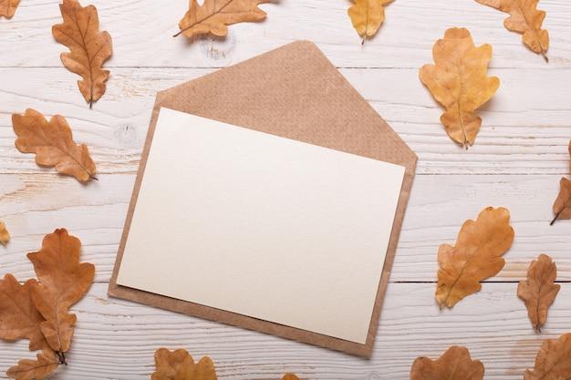 Foglie e busta di autunno su una tavola di legno bianca