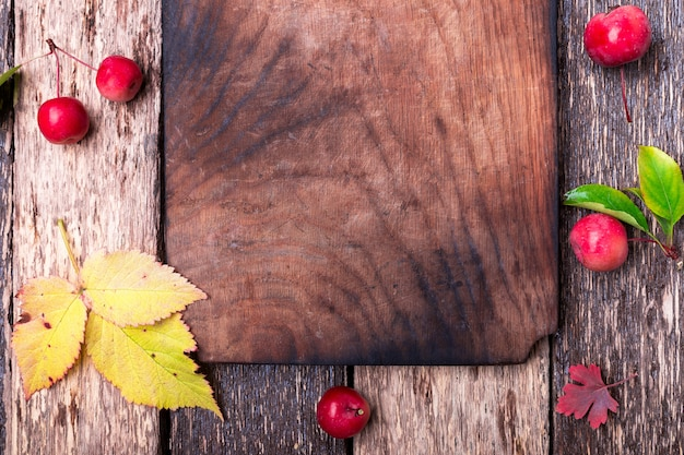 Foglie e piccola mela intorno al tagliere vuoto