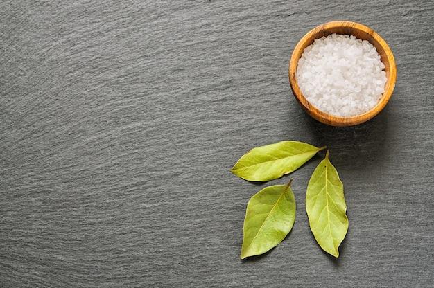 Foglie e sale semi secchi dell'alloro sulla pietra nera dell'ardesia con lo spazio della copia per testo come fondo dell'alimento. vista dall'alto