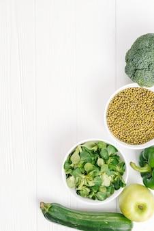Foglie fresche di insalata di mais; mela; broccoli; cetriolo e fagioli mung sulla scrivania bianca