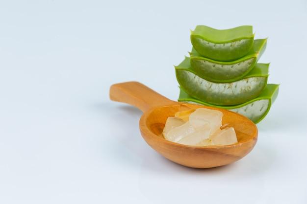 Foglie fresche di vera dell'aloe con le fette e gel sul cucchiaio di legno. l'aloe vera è l'uso naturale di erbe per la bellezza.