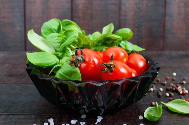 Foglie fresche verdi di basilico organico e piccoli pomodori e pepe maturi per una dieta sana.