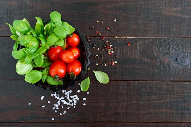Foglie fresche verdi di basilico organico e piccoli pomodori e pepe maturi su una tavola di legno per una dieta sana. vista dall'alto. spazio libero per il tuo progetto.