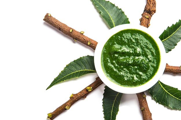 Foglie medicinali di neem con pasta in ciotola e ramoscelli