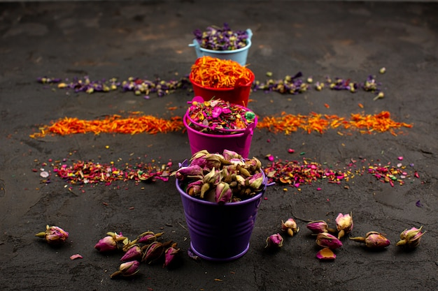 Foglie multicolori fiore e altre particelle colorate in vasi su una scrivania grigia