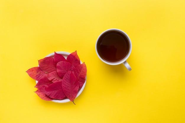 Foglie rosse autunnali e una tazza di caffè su uno sfondo giallo brillante