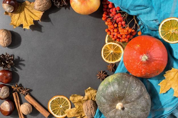 Foglie secche gialle, mele, noci, zucche, spezie, castagne e coni sul tavolo. mood autunnale, copyspace, distesi piatti.
