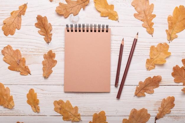 Foglie, taccuino e matite di autunno su un fondo di legno bianco. vista piana, vista dall'alto, copia spazio.