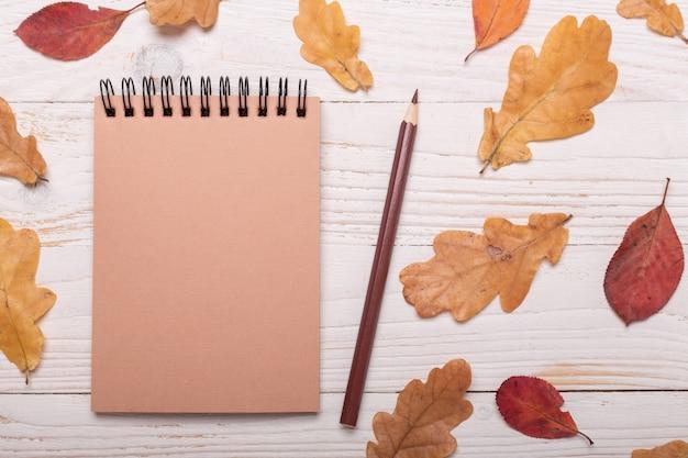 Foglie, taccuino e matite di autunno su una tavola di legno bianca