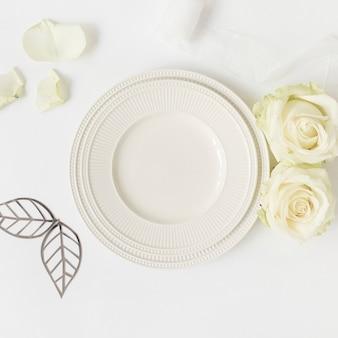 Foglie tagliate; rose e piatto di ceramica; nastro su sfondo bianco