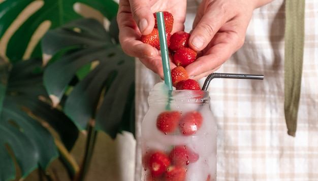 Foglie tropicali del ghiaccio del cocktail del fondo bianco della mano di vetro della bevanda della fragola