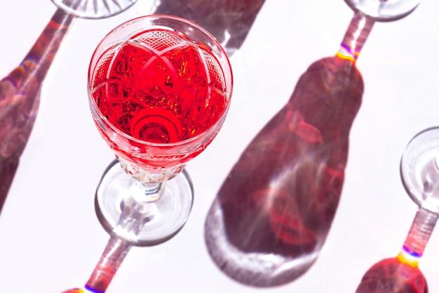 Foglie tropicali dell'ombra leggera del fondo di vetro bianco del vino rosso