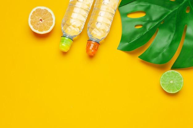 Foglie tropicali e acqua di bottiglia su fondo giallo. detox acqua infusa di frutta.
