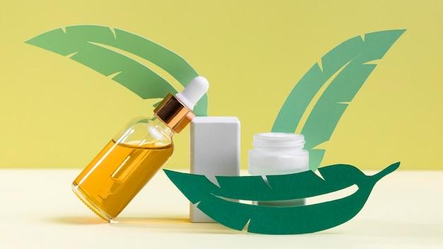 Foglie verdi con bottiglia di siero