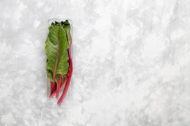 Foglie verdi fresche della barbabietola (barbabietola) in scatola di plastica su calcestruzzo grigio