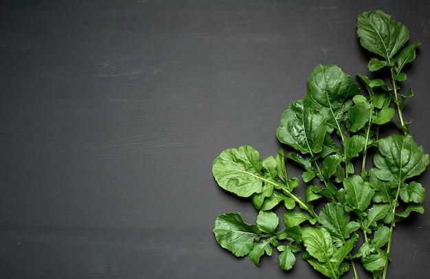 Foglie verdi fresche di rucola su un fondo di legno nero