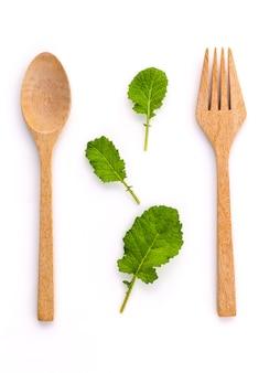 Foglie verdi organiche fresche di concetto sano dell'alimento con la forchetta ed il cucchiaio di legno.