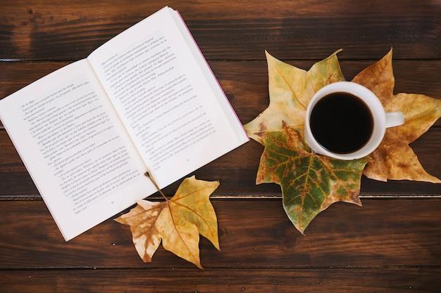 Foglie vicino al libro e tazza di caffè