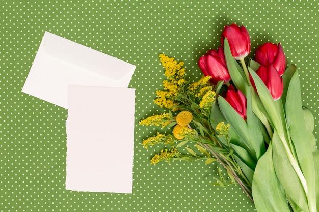 Foglio bianco; busta con fiori su sfondo verde sulla festa della mamma