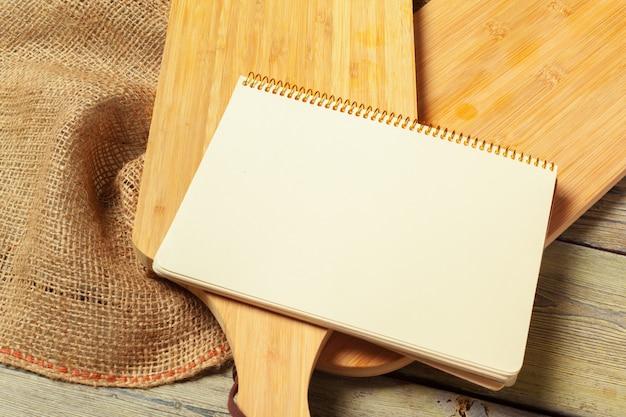 Foglio bianco degli utensili aperti della cucina e del blocco note sulla tavola con la tovaglia, spazio della copia