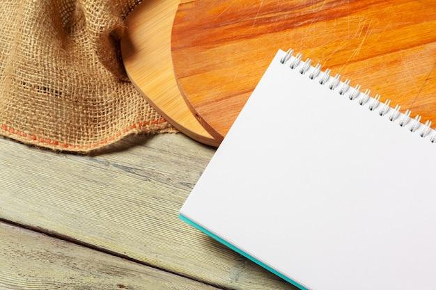 Foglio bianco del blocco note aperto e degli utensili della cucina sulla tavola con la tovaglia, spazio della copia