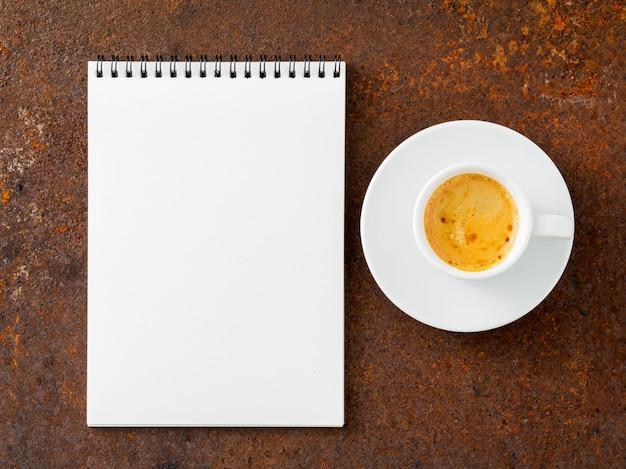 Foglio bianco del taccuino una spirale e una tazza di caffè sulla vecchia tavola arrugginita del ferro, vista superiore.