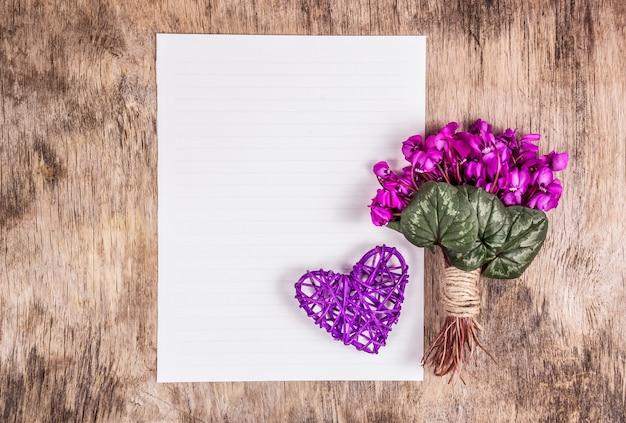Foglio bianco di carta, cuore e fiori.
