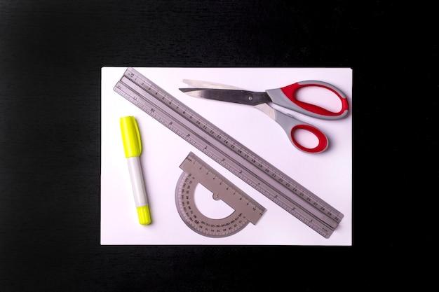 Foglio bianco di concetto di ritorno a scuola con gli strumenti su una lavagna nera