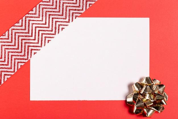 Foglio bianco e nastro su sfondo rosso