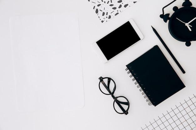 Foglio bianco; smartphone; occhiali; diario; matita e sveglia sulla scrivania bianca