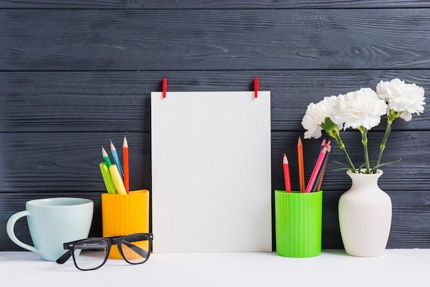 Foglio bianco; titolari; tazza; occhiali e vaso sullo scrittorio bianco contro fondo di legno