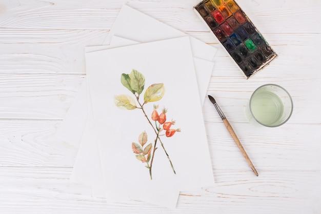 Foglio con vernice vegetale vicino a vetro, pennello e colori ad acqua