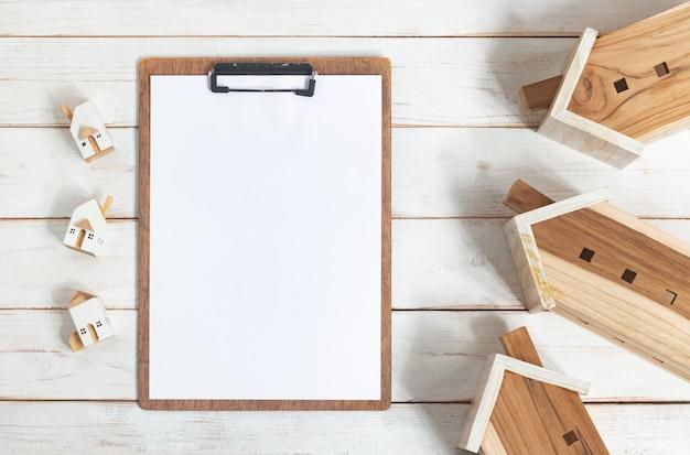 Foglio di calcolo su appunti e casa in legno in miniatura