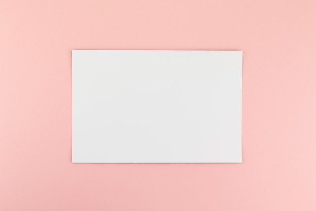 Foglio di carta a4 bianco su sfondo rosa