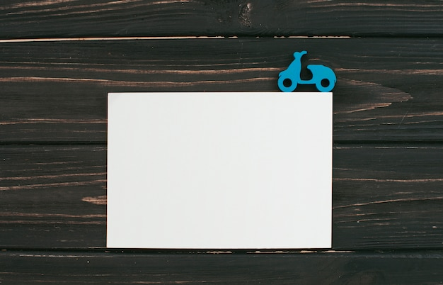 Foglio di carta bianca con piccolo motorino sul tavolo