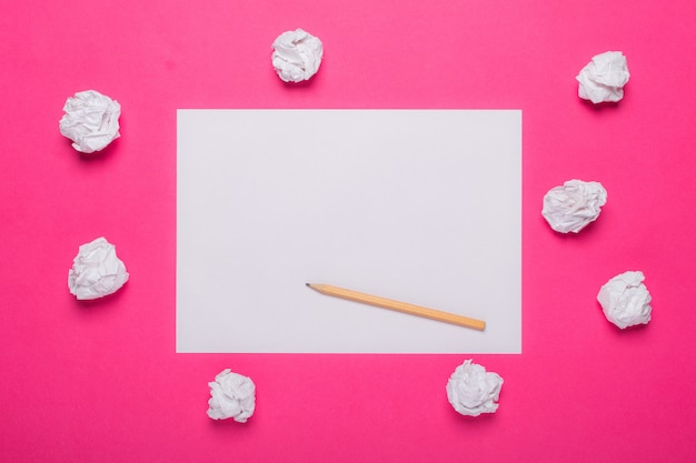 Foglio di carta bianco bianco, matita di legno e palline di carta stropicciata sul rosa