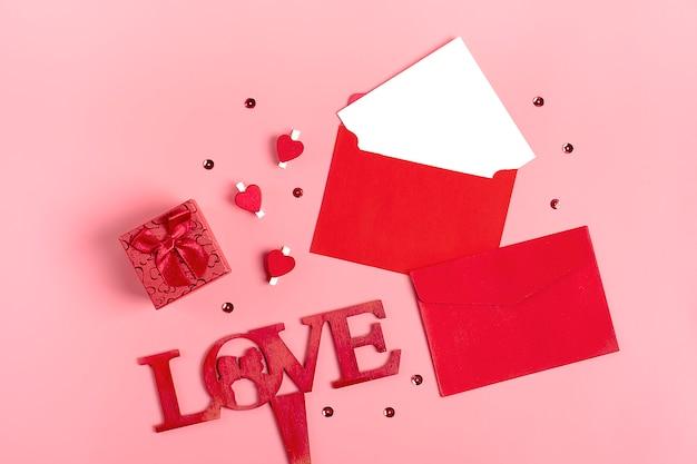 Foglio di carta bianco, busta rossa, scatola regalo, piccole scintille, penna su sfondo rosa
