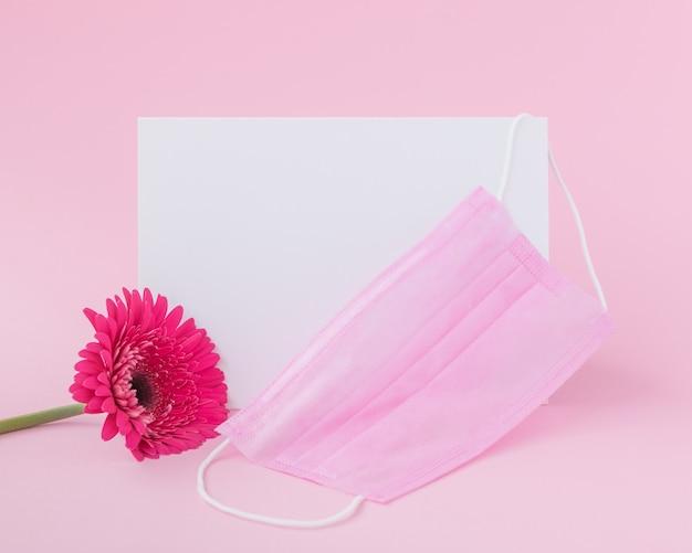 Foglio di carta bianco con maschera protettiva medica e fiore di gerbera rosa su sfondo rosa