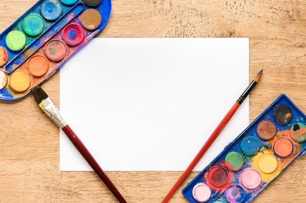 Foglio di carta bianco con tavolozza sulla scrivania